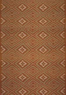 Interlocking hooks and diagonals create an allover symmetrical pattern in rust-brown, ivory, and pale blue-green.