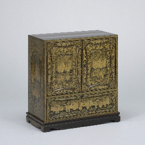 Small cabinet of lacquered wood painted in different tones of gold, pale green, and red.  The cabinet is made up of three rows of drawers set above a single long drawer, the three rows are hidden behind a pair of doors which peek out; the cabinet rests on a detachable footed stand.  The face of the doors and long drawer have a recessed rectangular panel each with curved edges and rolled curves. The panels are ornamented with scenes of figures grouped about buildings set in elaborate landscapes.
