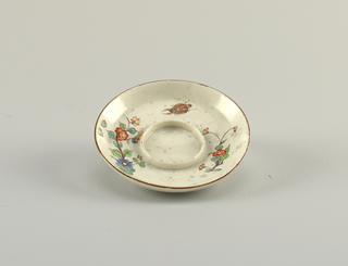 Curved sides, raised rim at centre. Decorated with indianische blumen (Indian flowers); outer rim painted brown.