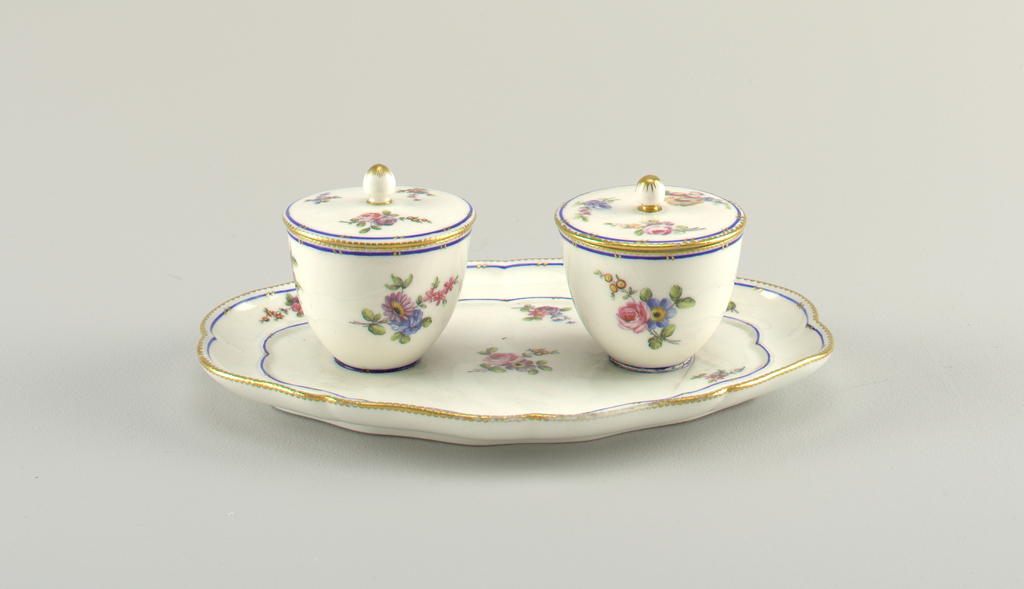 Oval tray with shaped edge. Two cups and flat covers with oblong knobs. Decoration of scattered floral sprays and blue bands.