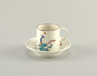 A white cup and saucer with a very cynlidrcal form. Both painted with a bird and flowers.