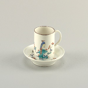 A white cup and saucer with a very cylidrcal form. Both painted with a bird and flowers.