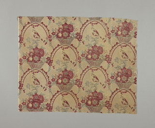 Birds rest on branches that extend from basket or vase full of flowers. Above birds are ribbon-like swags that form half-circles. Half-drop repeat printed in red, blue and black. Four minimum units across the width of fabric.