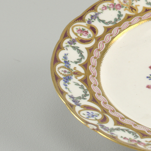 Circular molded plate with broad rim painted in purple ground with continuous enameled and gilded floral swags in blue, pink, and green, with gilded scallops. Center with floral border, gilded edge, and central spray ofroses against purple ground.