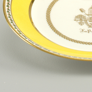 """Decorated in yellow, green, red and brown, with gilding. Flat bottom: slightly cavetto marly decorated with concentric bands of yellow and gold, edged with serpentine vine with berries. In bottom, gold laurel wreath enclosing a trophy composed of confections; caption below, in Gothic letters: """"Les Patisseries""""."""