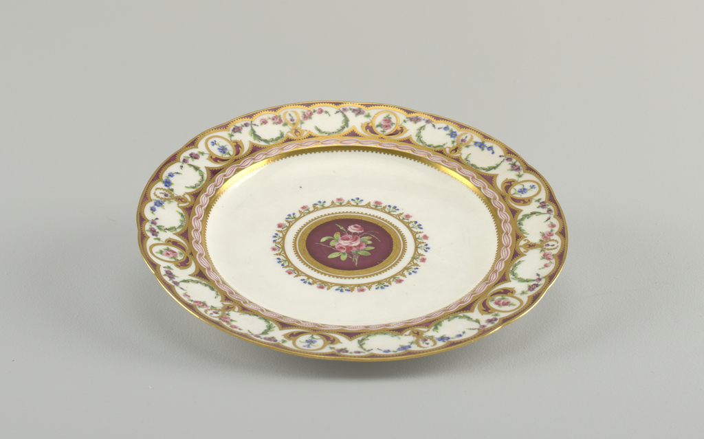 Circular molded plate with broad rim painted in purple ground with continuous enameled and gilded floral swags in blue, pink, and green, with gilded scallops. Center with floral border, gilded edge, and central spray of roses against purple ground.