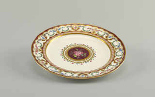 Circular molded plate with broad rim painted in purple ground with con- tinuous enameled and gilded floral swags in blue, pink, and green, with gilded scallops. Center with floral border, gilded edge, and central spray ofroses against purple ground.