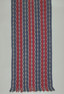 "Shawl of blue and red stripes with narrow blue and white ""jaspeado"" bands. Warp selvage at one end. Warp fringe at the other end has been knotted with silk added at the end of each red stripe. Knotted sections form tabs of various widths. Note use of red weft."