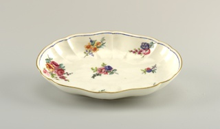 Oval slightly scalloped sides. Decorated with floral sprays. Slim blue band on inside edge. Top edge gilded.