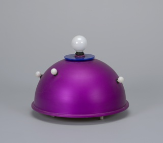 Bright pink-purple dome-shaped aluminum lamp topped with blue disc and large globular white light bulb; smaller globular white bulbs scattered on body; circular base with casters; black cord with circular black foot switch.