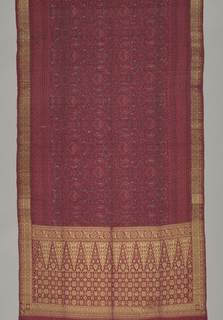 Complete sarong with two heavily brocaded ends showing the tumpal motif, triangles, and a small allover pattern of stars and rosettes. Central section of weft ikat predominantly in shades of red. Side borders have metal thread brocading.