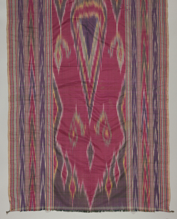 Vertically rectangular hanging with a vertically symmetrical pattern of a cyprus tree flanked by two smaller trees, birds at top of both trees, pointed arch at top. Left and right borders made up of stripes and ikat chevron stripes. Deep red of the field predominates.