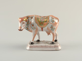 Standing cow with head turned to the left. On an elongated octagonal base with beveled sides. Painted decoration including a blanket and sprays of flowers in green, pink, red and gold.