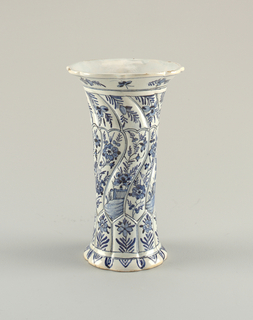 Tall, twisted, fluted 8-sided vase with short flared foot and flaring mouthwith shaped rim; painted in underglaze blue on white with 8 vertical panelseach with flower bottom, alternate mid-sections of landscapes or flowers, top sections of flowers.