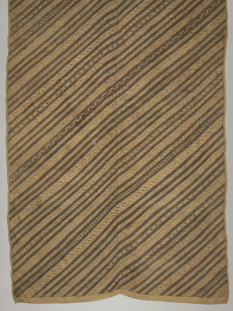 """A long sarong (kain panjang) with varied diagonal stripe (""""garis miring"""") pattern in brown. Diagonals show different patterns within the stripes, some of which are repeated."""