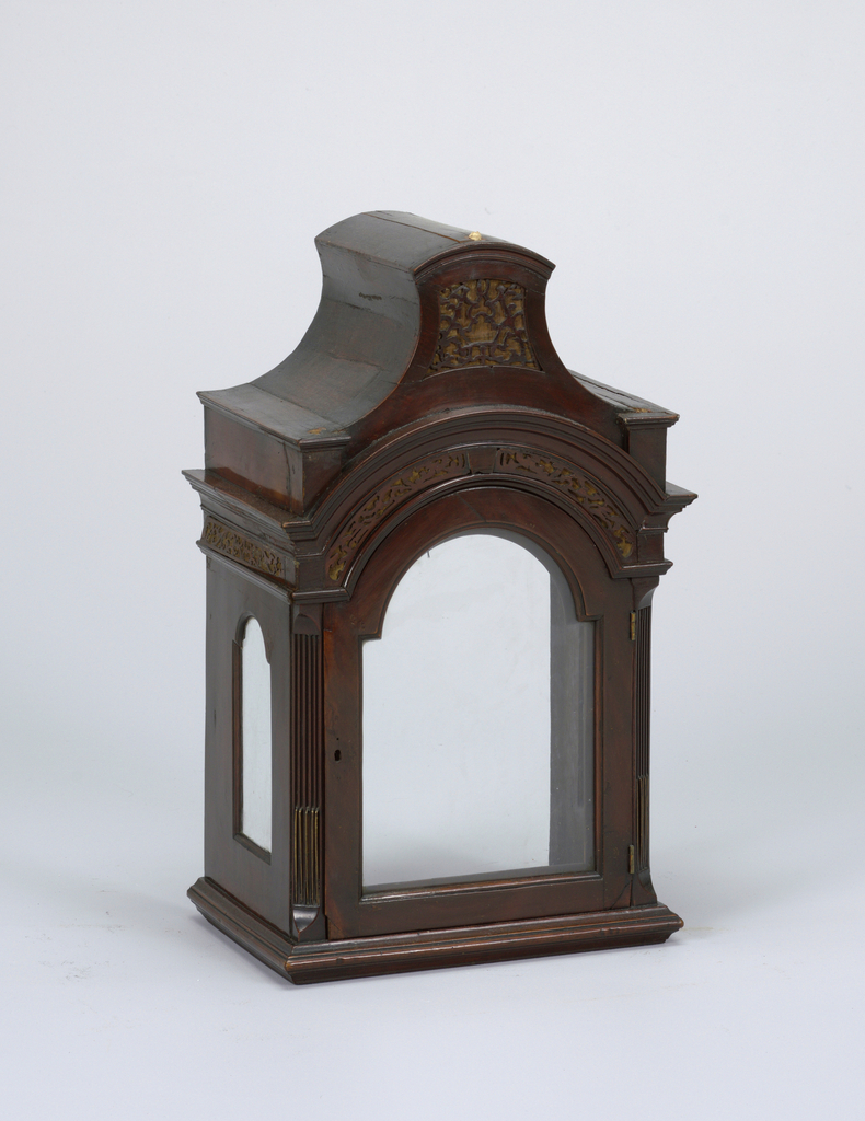 Rectangular base resting on moulding and slight feet. On front, moulding in shaoe of rectangle with concave corners. Slender case with arched door. Clock house projecting, with cut, fluted corners, arched glass windows on side, and arched door. Above, cut-out scrollwork below concave arched top, and three brass urn-and-flame- finials. Brass face partly engraved, deocrated with applied scrolls. Four white enamel ring dials and name plate.