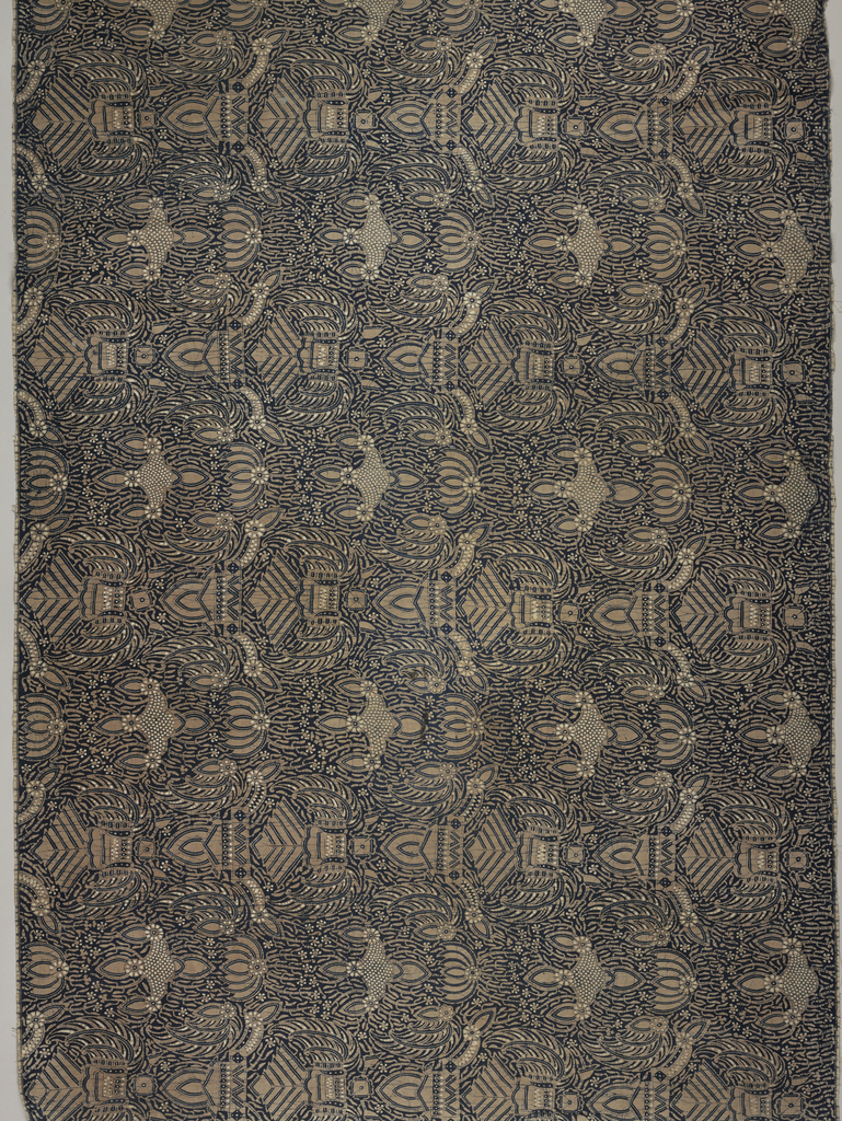 """Long batik sarong (kain panjang) in dark blue, light brown, and white. Dark blue ground showing numerous white dots known as """"gabah sinawur"""" (grains of rice). The """"semen"""" (curling tendrils and other non-geometric forms) and """"sawat"""" (wings and tail of Garuda, mount of Vishnu) motifs, mountains, and crowns are also used."""