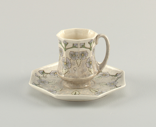 Cup (a) 8-sided body, cinched slightly at center with C-curved handle. Saucer (b) octagonal dish with upcurved edges. Both decorated with violet flowers, light green jagged leaves, green stems with violet flower buds, all on gray ground.
