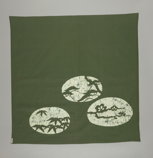 Dark green cloth with three ovals in reserve white with the three symbols of marriage—fir, plum and bamboo—in same dark green color. Mock paste resist crackling print in dark green and blue-gray.