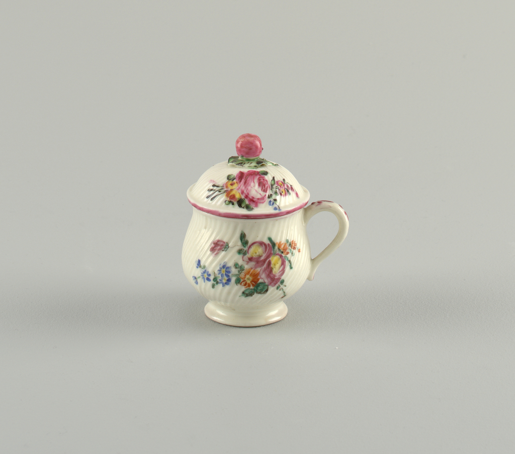 Cup full-bellied, with spiral ribbing and simple loop handle; domed, with twisted ray ribbing and knob in form of an apple with leaves. Decorated with floral sprays.