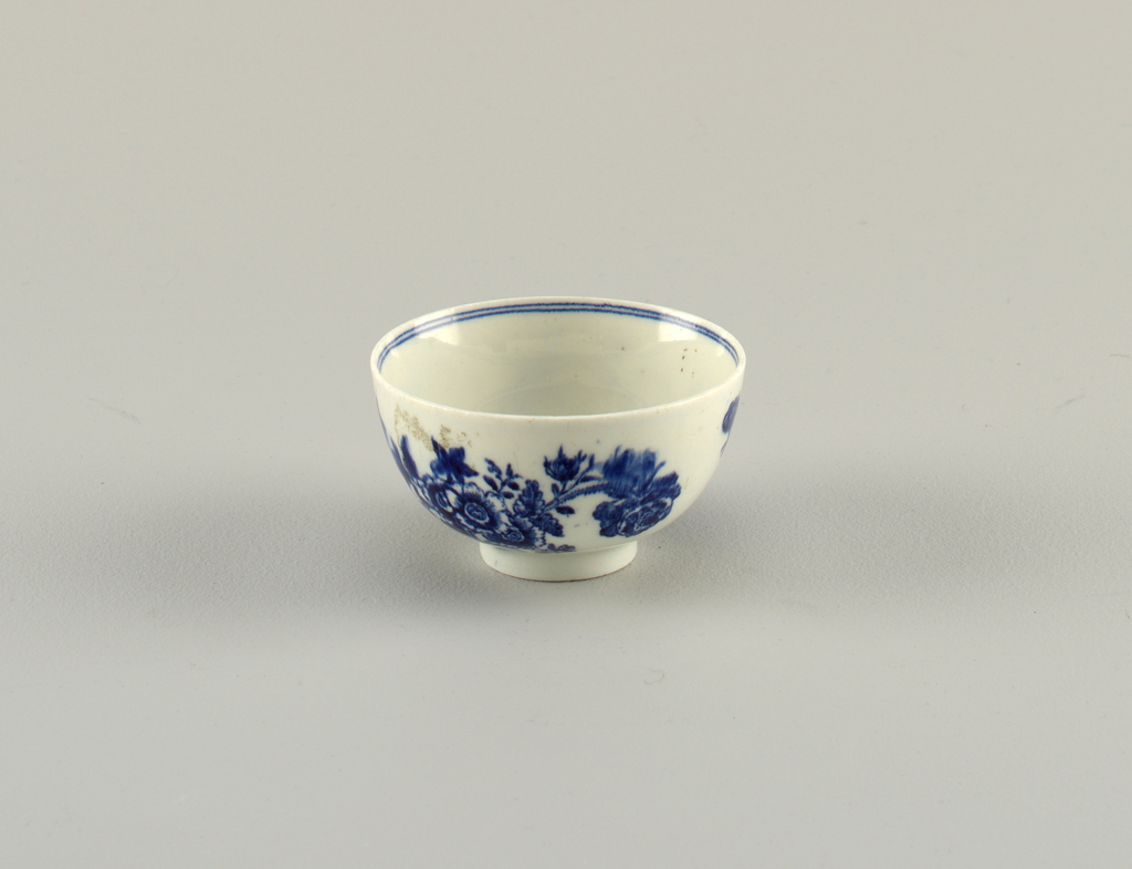 Round cup, no handle, on high foot. Blue floral decoration on exterior. Double line on inner rim.