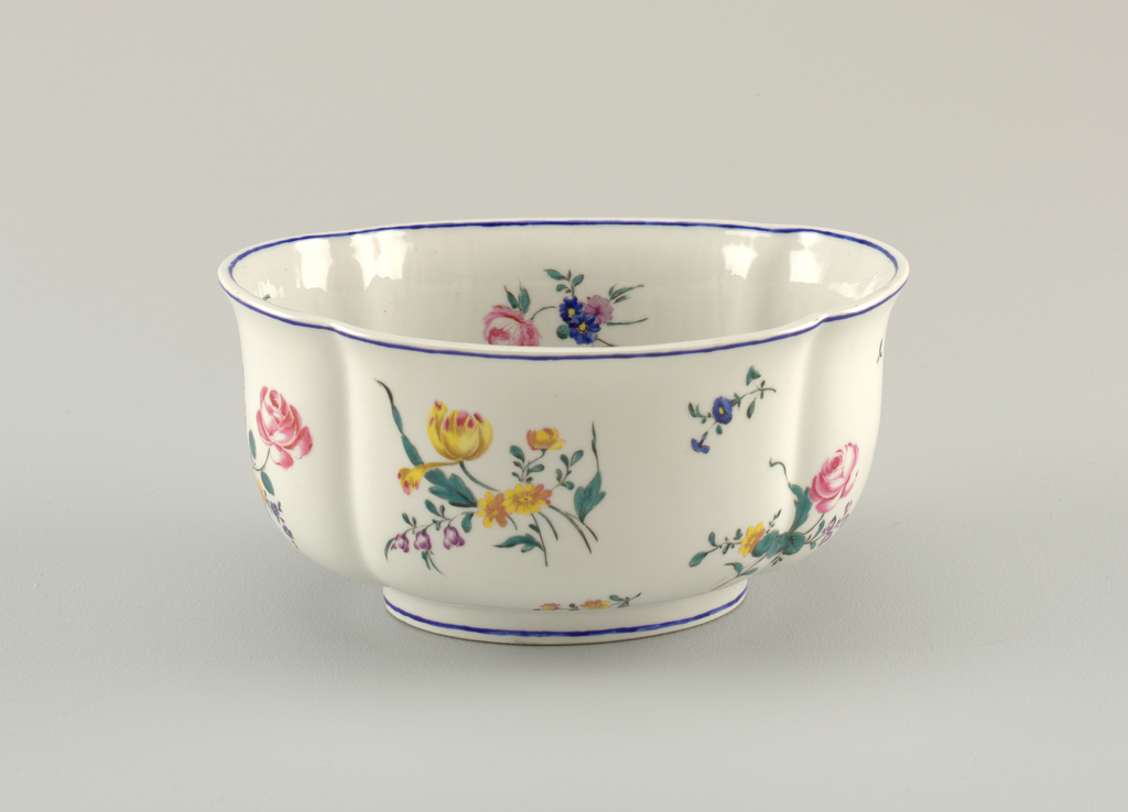 """Four-lobed oval, with curved, flaring sides, on straight foot. Polychrome overglaze clusters and sprays of flowers scattered over inside and outside. Blue band on inner and outer edge and foot. Marked """"DV"""" (in overglaze purple)."""