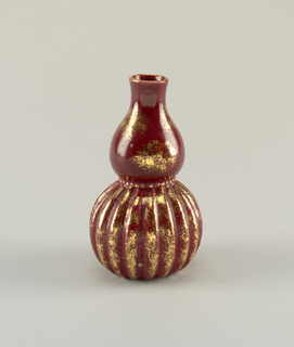 Double-gourd shape, ribbed lower section, band of impressed beading, painted gold, between two sections of body. Red glaze mottled with gold.