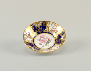 Saucer interior with segmented decoration of gilt and enamel florals on alternating white and blue ground. Gilding at rim.