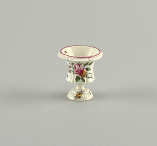 A molded footed vase. Hand-painted floral spray on body; pink at rim. Spiral molding on foot.