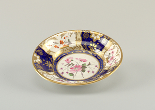 Dish with segmented decoration of gilt and enamel florals on alternating white and blue ground. At center, a white medallion with pink flowers. Gilding at rim.