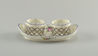 A low, oblong dish with blue rim and scattered flowers. Two openwork vessels with blue glaze on the undulating rim and outlining the lattice work.