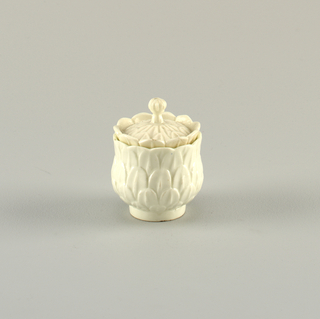 On plain foot, an inverted bell-shaped cup; the outside covered with relief-cut artichoke leaves, forming scalloped edge above inner rim. Cover with slight dome, covered with relief-cute artichoke leaves, and a row of standing leaves around edge. Four-leaf knob finial. Undecorated.