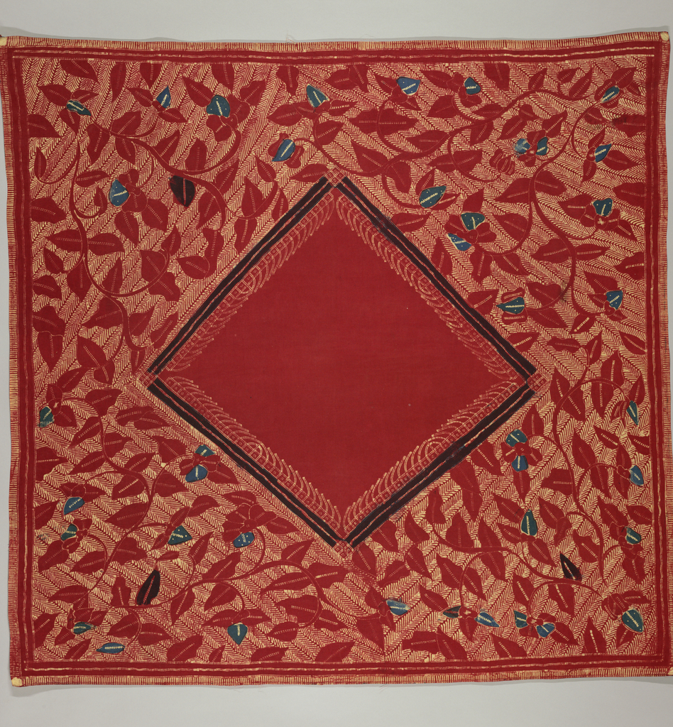 Square headcloth (kain kepala) or carrying cloth in red, blue, and cream. Plain red diamond center with white line design at edges and bordered in blue. Diamond surrounded by a red floral vine in on a herringbone ground. Narrow plain outer border in red and outer imitating fringe.