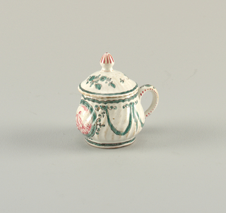A custard pot with one handle; molded spirals on body. A lid, also with spirals, and a tall finial. Hand-painted enamel decoration showing green florals and swags, and an oval cartouche was a pink monochrome scene of a cherub.