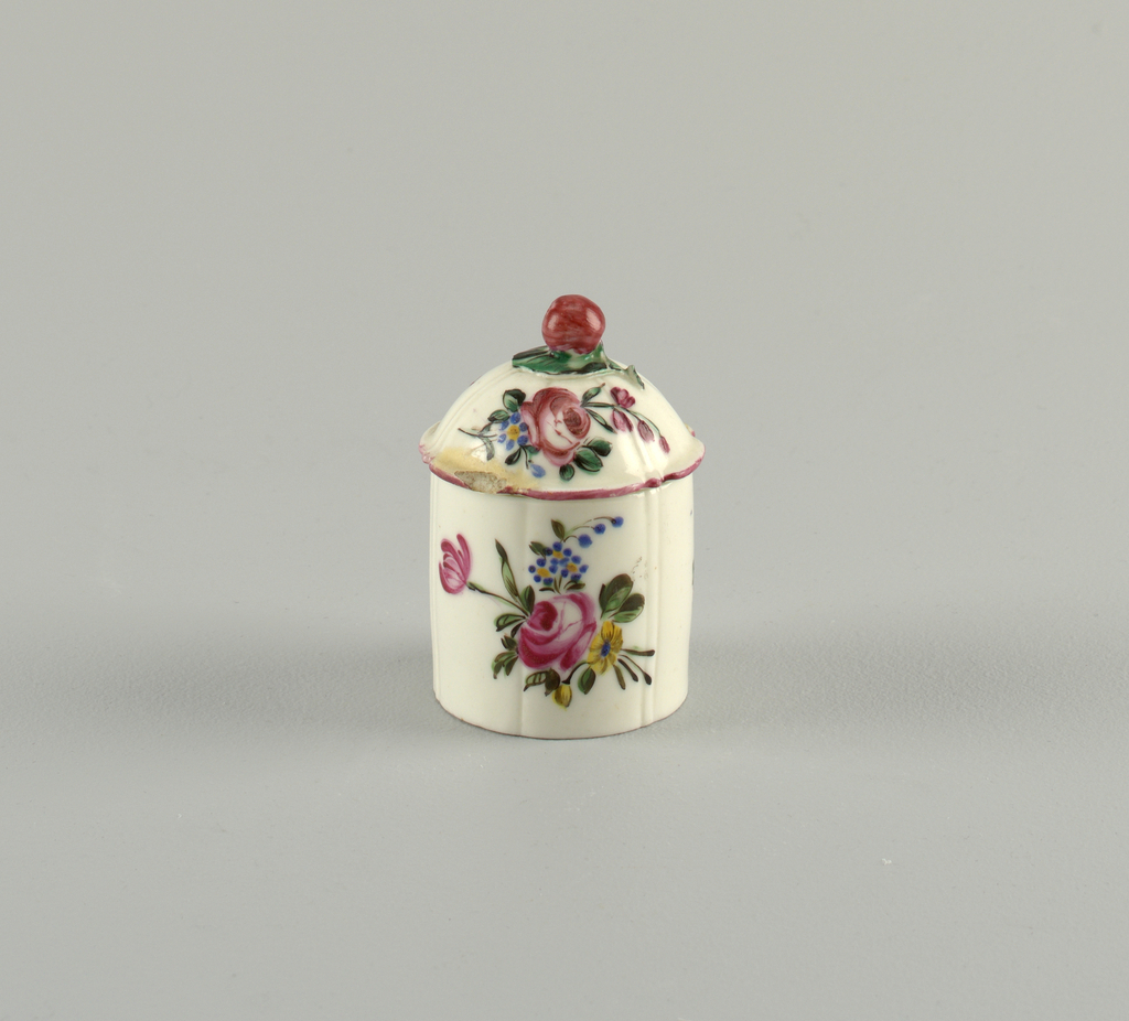 Lobed body painted with a large floral spray. Dome lid topped with a fruit, pink at rim.