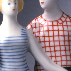 Boy with red checked shirt and dark pants stants next to girl with blue striped dress; he holds her left hand in his.