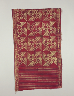 Part of a child's sarong with design, in red, or borders and squares ornamented with triangles and lozenges.