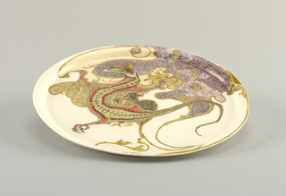 Circular plate with curved dragon motif in center.