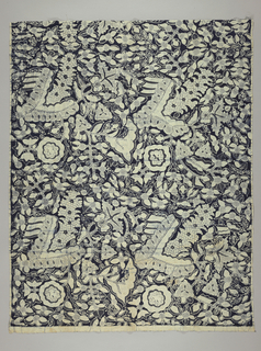 Length of batik fabric with bold, dense, and varied all-over floral repeat in ivory (with crackle) on a dark blue ground. Some flowers and leaves show grid, parallel line, as well as gringsing (fish scale-like) details.