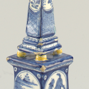 Four-sided obelisk with molded bottom edge, ball finial, four ball feet; square base with molded top and bottom edges, four ball feet; painted in underglaze blue and yellow, on base with roundels each side, each with dragon or landscape, on top with reserves of flowers and landscapes.