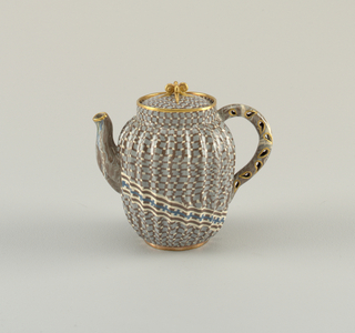 Ribbed ovoid teapot with gingham pattern in black and white over light blue; band crossing body in white and black with blue crosshatch pattern. Gilt-rimmed lid and spout; loop handle with gilt-rimmed teardrop cutouts.