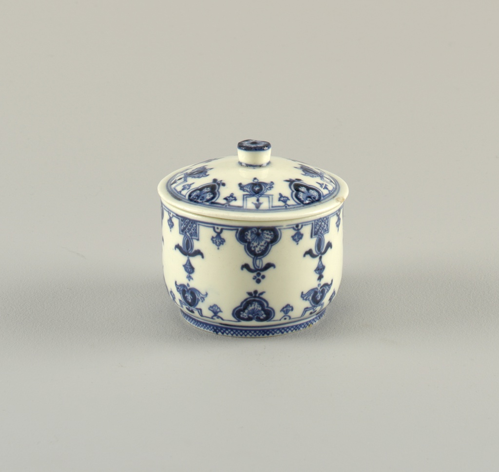 A) Circular box on narrow foot, with straight sides B) Slightly domed cover with simple knob. Box and cover decorated with underglaze blue lambrequin design.