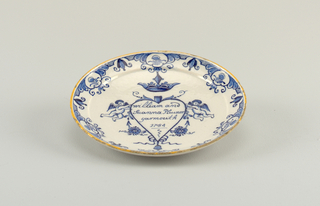 "Circular plate with up-curving rim; back dome shaped, flattened at center; painted in underglaze blue and yellow on white with a heart surmounted by a crown and surrounded by putti and flowers, inscribed inside ""William and / Suanna Plumer / Yarmouth / 1754""; a stylized floral border with yellow rim."