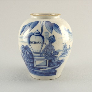 """Ovoid body, short neck with everted rim; painted in underglaze blue on white with American Indian smoking a pipe, next to a large jar inscribed """"Schosse,"""" large tobacco plant overhead, crates and barrels left, one inscribed """"VOC,"""" two sailing ships on right."""