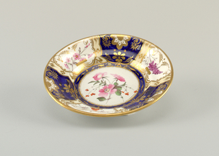 Dish with segmented decoration of gilt and enamel florals on alternating white and blue ground. At center, a white ground medallion with pink flowers. Gilding at rim.