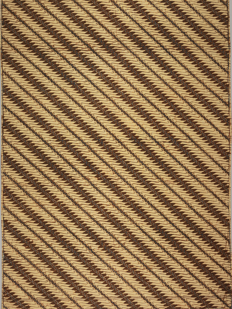 """Panel of cotton batik printed in diagonally-arranged pattern of hook-shaped motif known as """"parang tuding"""" in reddish brown and accented with blue dots on tan. Because it is arranged along a diagonal, the pattern falls in the """"garis mirig"""" category. One weft band with black stripe surrounded by a thin red strip on each side visible under batiked pattern."""