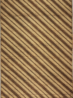 "Panel of cotton batik printed in diagonally-arranged pattern of hook-shaped motif known as ""parang tuding"" in reddish brown and accented with blue dots on tan. Because it is arranged along a diagonal, the pattern falls in the ""garis mirig"" category. One weft band with black stripe surrounded by a thin red strip on each side visible under batiked pattern."