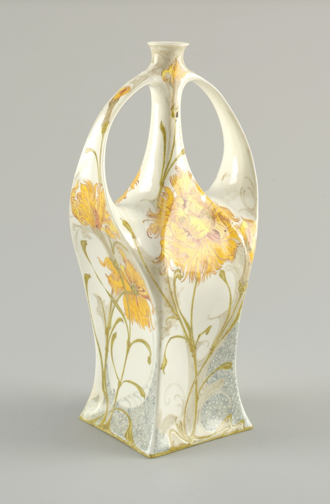 Bottle form with square base, each of 4 sides slightly concave with two sides rising to curved, strap-like handles that branch out from shoulders and join bottle just beneath small curved lip at top of long narrow neck; surface features painted decoration of delicate, stylized carnations with attenuated stems in yellow, green, and rust tones; a pale blue speckle-like pattern is painted in areas near lower half, all painted on off-white ground.
