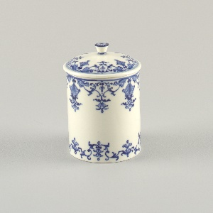 Cylindrical form featuring arabesque or lambrequin motifs wrapped around entire circumference of pot on both upper and lower edges, all in underglaze blue; similar motif wrapped around edge of lid; knob on top of lid features single fower motif; all on white ground.
