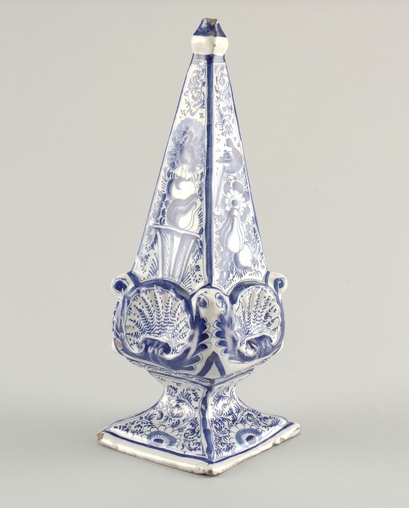 Four-sided obelisk with molded shell and scroll ornaments at base of each side, finial at top, splayed foot; painted in underglaze blue, the sides with fruit and birds, the base with floral/leaf scrolls.